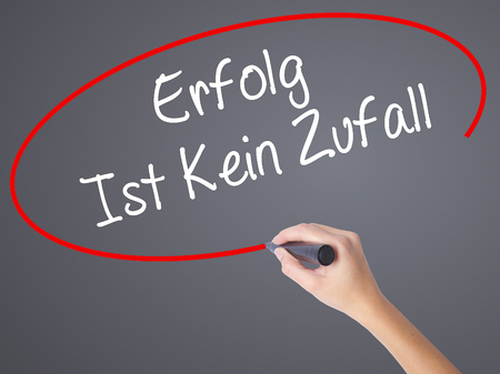 Woman Hand Writing Erfolg Ist Kein Zaufall (Success Is No Accident in German) with black marker on visual screen. Isolated on grey. Business concept. Stock Photo
