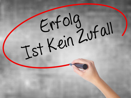 Woman Hand Writing Erfolg Ist Kein Zaufall (Success Is No Accident in German) with black marker over transparent board. Isolated on grey. Business concept. Stock Photo