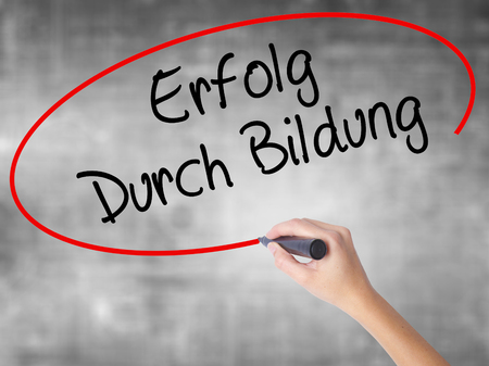 Woman Hand Writing Erfolg Durch Bildung  (Success Through Training in German) with black marker over transparent board. Isolated on grey. Business concept. Stock Photo