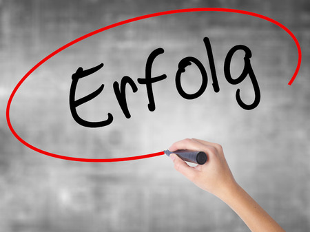 Woman Hand Writing Erfolg Success (in German) with black marker over transparent board. Isolated on grey. Business concept. Stock Photo