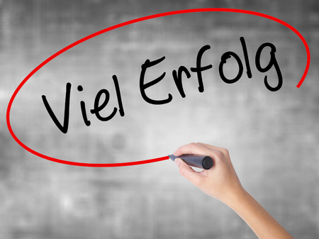 Man Hand writing Viel Erfolg (Much Success In German) with black marker on visual screen. Isolated on background. Business, technology, internet concept. Stock Photo