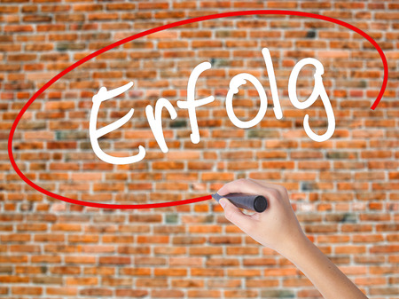 Woman Hand Writing Erfolg Success (in German) with black marker on visual screen. Isolated on bricks. Business concept. Stock Photo