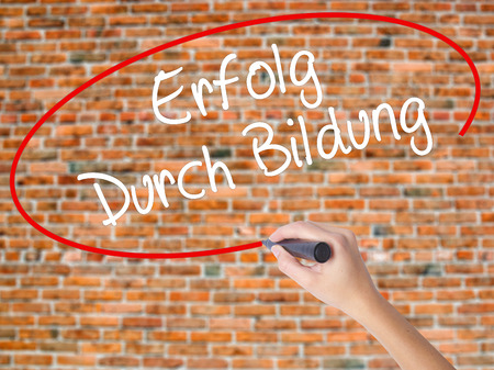 Woman Hand Writing Erfolg Durch Bildung  (Success Through Training in German) with black marker on visual screen. Isolated on bricks. Business concept. Stock Photo