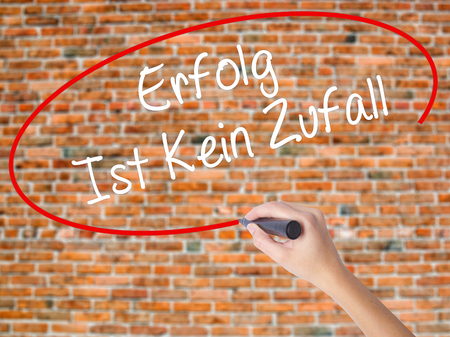 Woman Hand Writing Erfolg Ist Kein Zaufall (Success Is No Accident in German) with black marker on visual screen. Isolated on bricks. Business concept. Stock Photo