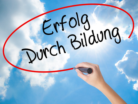 Woman Hand Writing Erfolg Durch Bildung  (Success Through Training in German) with black marker on visual screen. Isolated on Sunny Sky. Business concept. Stock Photo