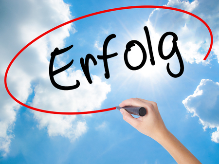 Woman Hand Writing Erfolg Success (in German) with black marker on visual screen. Isolated on Sunny Sky. Business concept. Stock Photo
