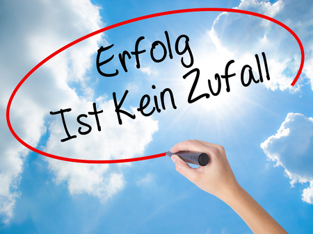 Woman Hand Writing Erfolg Ist Kein Zaufall (Success Is No Accident in German) with black marker on visual screen. Isolated on Sunny Sky. Business concept. Stock Photo