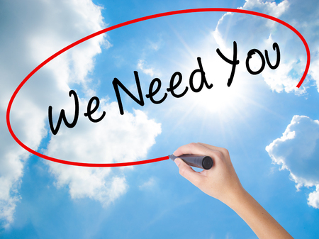 Foto de Woman Hand Writing We Need You with black marker on visual screen. Isolated on Sunny Sky. Business concept. Stock Photo - Imagen libre de derechos