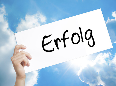 Man Hand Holding Paper with text Erfolg Success (in German) . Sign on white paper. Isolated on Sky background.   Business concept. Stock Photo