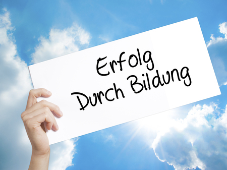 Man Hand Holding Paper with text Erfolg Durch Bildung  (Success Through Training in German) . Sign on white paper. Isolated on Sky background.  Business concept. Stock Photo