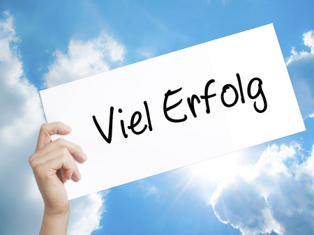 Man Hand Holding Paper with text Viel Erfolg (Much Success In German) . Sign on white paper. Isolated on Sky background.  Business concept. Stock Photo