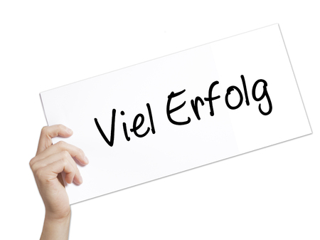 Viel Erfolg (Much Success In German) Sign on white paper. Man Hand Holding Paper with text. Isolated on white background.  Business concept. Stock Photo