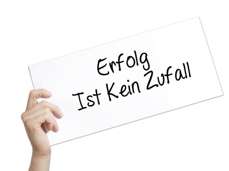 Erfolg Ist Kein Zaufall (Success Is No Accident in German) Sign on white paper. Man Hand Holding Paper with text. Isolated on white background.  Business concept. Stock Photo