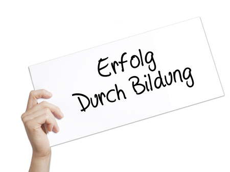 Erfolg Durch Bildung  (Success Through Training in German) Sign on white paper. Man Hand Holding Paper with text. Isolated on white background.  Business concept. Stock Photo