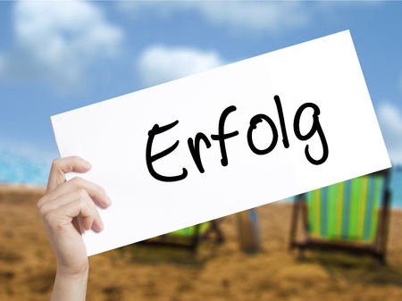 Erfolg Success (in German) Sign on white paper. Man Hand Holding Paper with text. Isolated on holiday background.   Business concept. Stock Photo