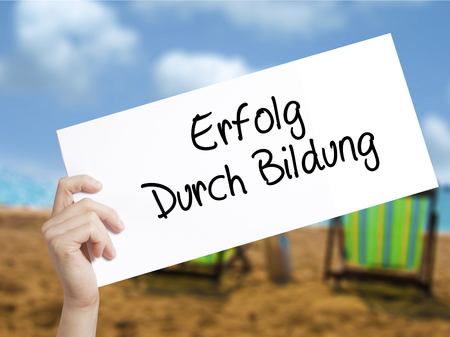 Erfolg Durch Bildung  (Success Through Training in German) Sign on white paper. Man Hand Holding Paper with text. Isolated on holiday background.  Business concept. Stock Photo