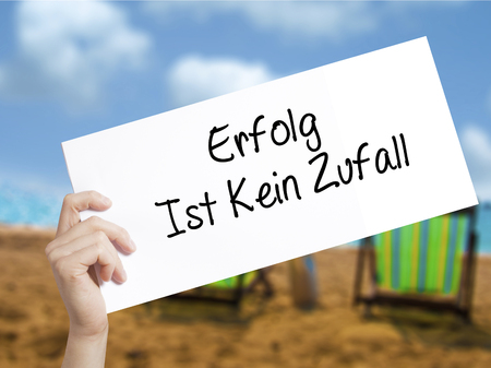 Erfolg Ist Kein Zaufall (Success Is No Accident in German) Sign on white paper. Man Hand Holding Paper with text. Isolated on holiday background.  Business concept. Stock Photo