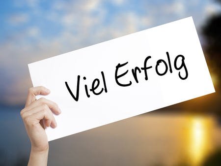 Viel Erfolg (Much Success In German) Sign on white paper. Man Hand Holding Paper with text. Isolated on sunset background.  Business concept. Stock Photo