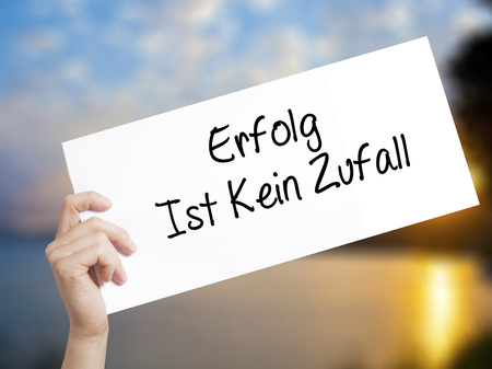 Erfolg Ist Kein Zaufall (Success Is No Accident in German) Sign on white paper. Man Hand Holding Paper with text. Isolated on sunset background.  Business concept. Stock Photo