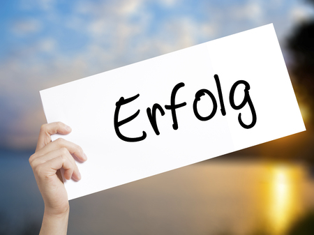 Erfolg Success (in German) Sign on white paper. Man Hand Holding Paper with text. Isolated on sunset background.   Business concept. Stock Photo