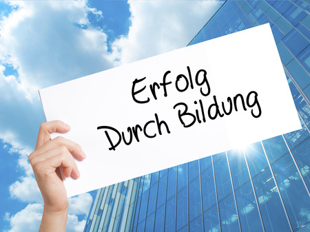 Erfolg Durch Bildung  (Success Through Training in German) Sign on white paper. Man Hand Holding Paper with text. Isolated on Skyscraper background.  Business concept. Stock Photo