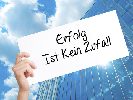 Erfolg Ist Kein Zaufall (Success Is No Accident in German) Sign on white paper. Man Hand Holding Paper with text. Isolated on Skyscraper background.  Business concept. Stock Photo