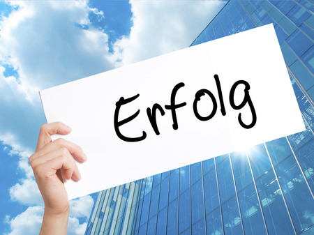 Erfolg Success (in German) Sign on white paper. Man Hand Holding Paper with text. Isolated on Skyscraper background.   Business concept. Stock Photo