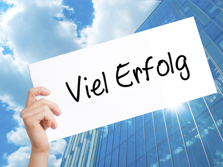 Viel Erfolg (Much Success In German) Sign on white paper. Man Hand Holding Paper with text. Isolated on Skyscraper background.  Business concept. Stock Photo
