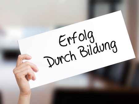 Erfolg Durch Bildung  (Success Through Training in German) Sign on white paper. Man Hand Holding Paper with text. Isolated on Office background.  Business concept. Stock Photo