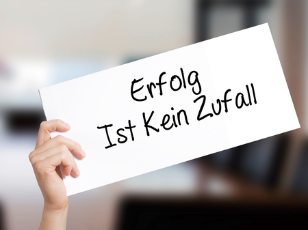 Erfolg Ist Kein Zaufall (Success Is No Accident in German) Sign on white paper. Man Hand Holding Paper with text. Isolated on Office background.  Business concept. Stock Photo