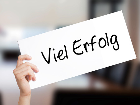 Viel Erfolg (Much Success In German) Sign on white paper. Man Hand Holding Paper with text. Isolated on Office background.  Business concept. Stock Photo