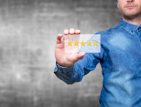 Foto de Man holding five star rating. Five stars service. Grey background - Stock Image - Imagen libre de derechos