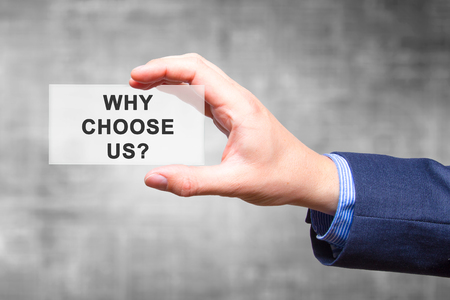 Foto de Businessman hand holding Why Choose Us? sign isolated on grey background. Business concept. Stock Photo - Imagen libre de derechos