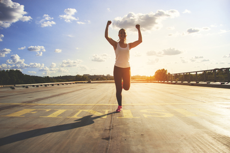 Photo pour Winner as style of life. Horizontal shot of young beautiful woman in sports clothing keeping arms raised and smiling while passing finish line during jogging. Evening sunlight on background. - image libre de droit