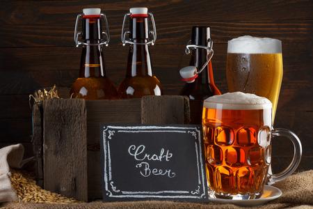 Foto de Craft beer glass and vintage wooden crate with beer bottles on burlap cloth with barley seeds - Imagen libre de derechos