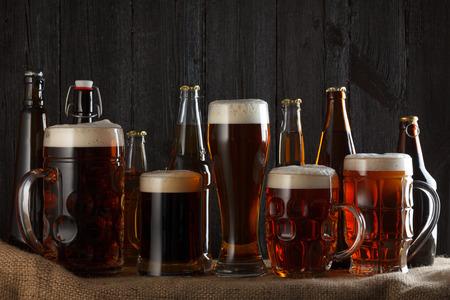 Foto de Beer glasses and bottles with lager, dark lager, brown ale, malt and stout beer on table, dark wooden background - Imagen libre de derechos