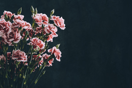 Foto de Carnation flowers bouquet vintage color toned. Dark moody background with copy-space. - Imagen libre de derechos