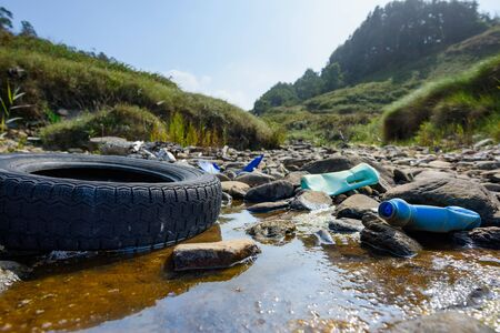 Photo for Earth plastics pollution global enviroment emergency. Old car tire in dirty water with plastic bottles and trash.  - Royalty Free Image