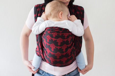 Photo for A cropped view of a baby in a woven wrap. A front view of a babywearing mother carrying her small child in a sling. - Royalty Free Image