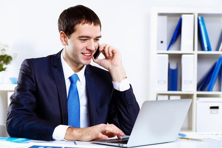 Young smiling happy businessman at work in office