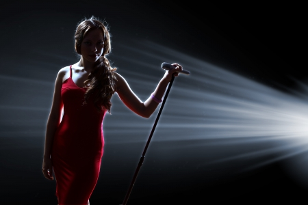Photo for Female singer on the stage holding a microphone - Royalty Free Image