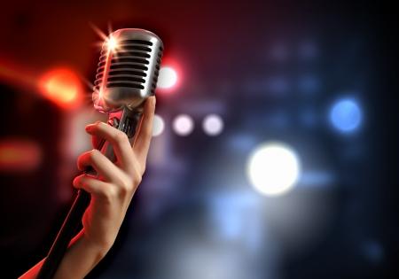 Photo pour Female hand holding a single retro microphone against colourful background - image libre de droit