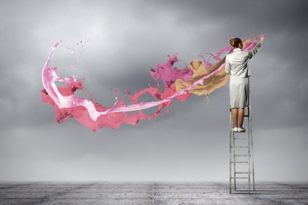 Photo pour Young woman standing on ladder drawing splashes with finger - image libre de droit