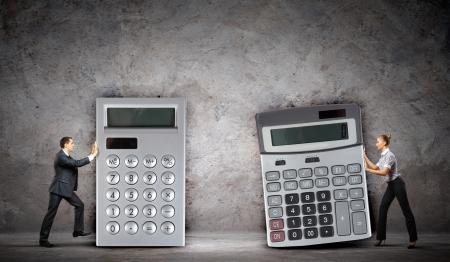 Photo pour Image of two businesspeople with big calculators - image libre de droit