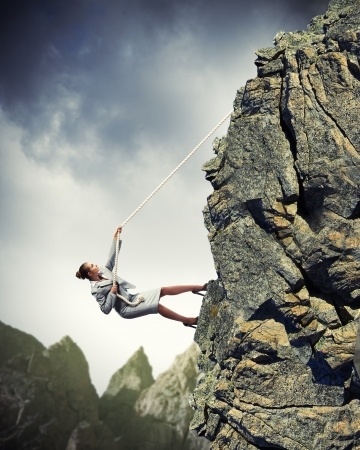 Photo for businesswoman climbing steep mountain hanging on rope - Royalty Free Image