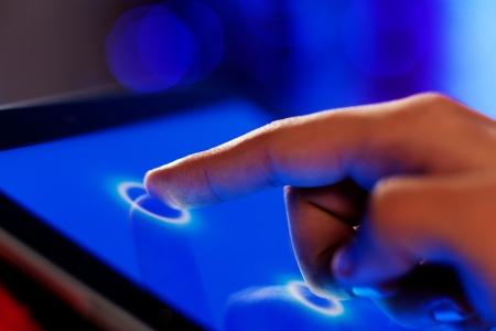 Foto de Close-up image of finger touching blue screen - Imagen libre de derechos