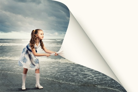 Foto de Little girl turning page with another reality - Imagen libre de derechos