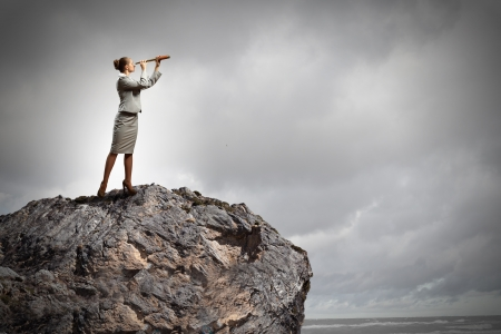 Photo for Image of businesswoman looking in telescope standing atop of rock - Royalty Free Image