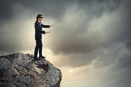 Foto de Image of businessman in blindfold standing on edge of mountain - Imagen libre de derechos