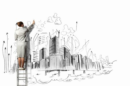 Photo pour Businesswoman standing on ladder and drawing sketch on wall - image libre de droit